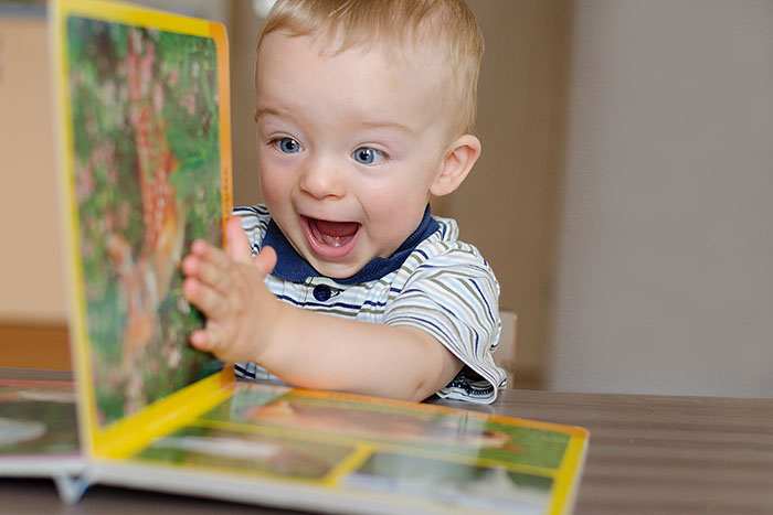 Baby boy turns the page in the book at a Preschool & Daycare Serving Fort Erie, CO, Kansas City, KS