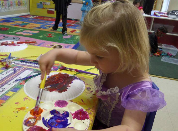 young girl painting at a Preschool & Daycare Serving Fort Erie, CO, Kansas City, KS