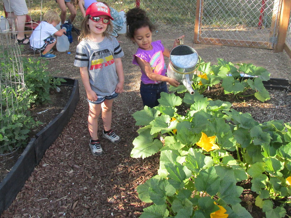 young girls smiling in a garden at a Preschool & Daycare Serving Fort Erie, CO, Kansas City, KS
