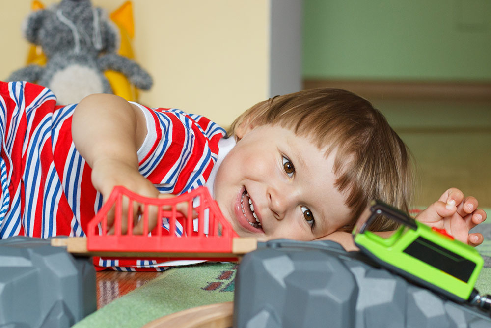 Little child playing with wooden train and tracks at a Preschool & Daycare Serving Fort Erie, CO, Kansas City, KS