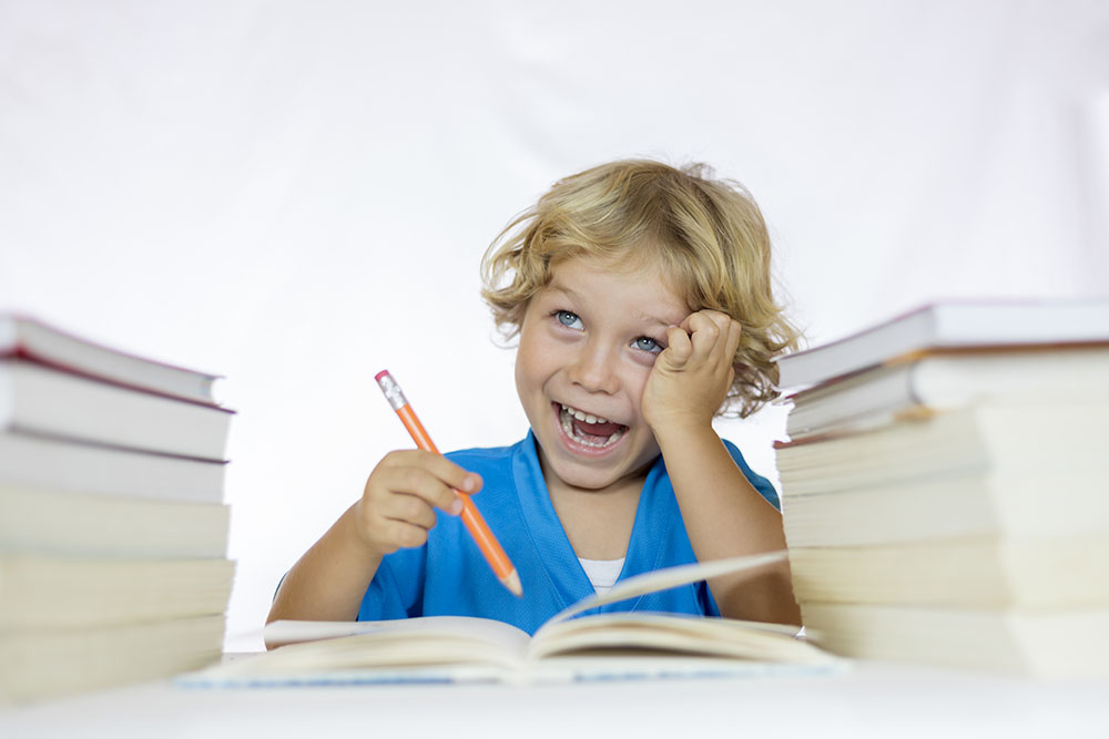 Little happy child sitting at a desk studying at a Preschool & Daycare Serving Fort Erie, CO, Kansas City, KS