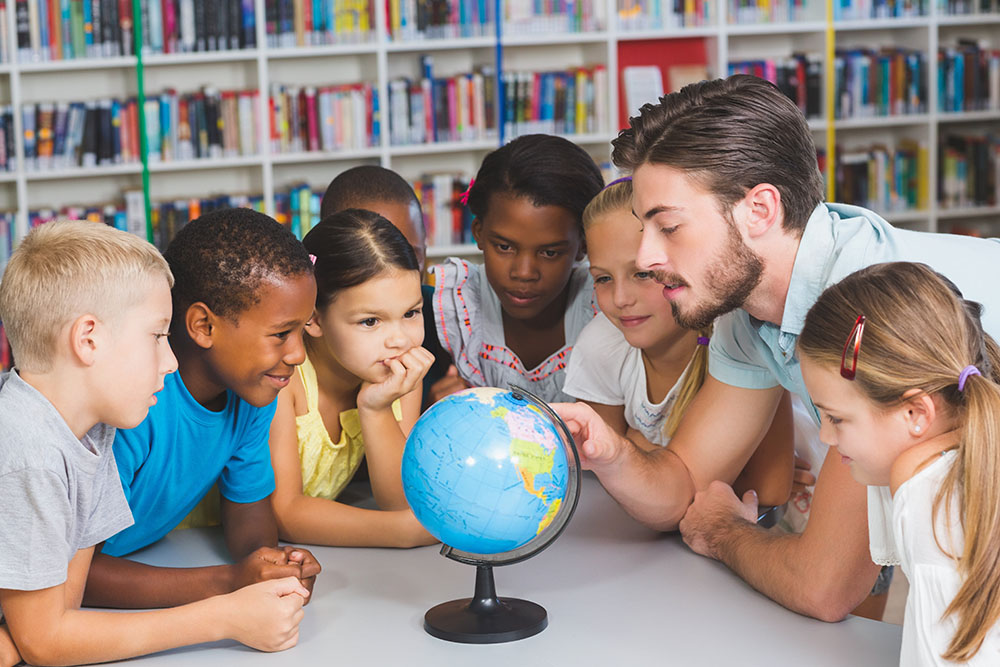 Students and teacher learning the globe in library at a preschool & childcare center Serving Erie, CO & Kansas City, KS