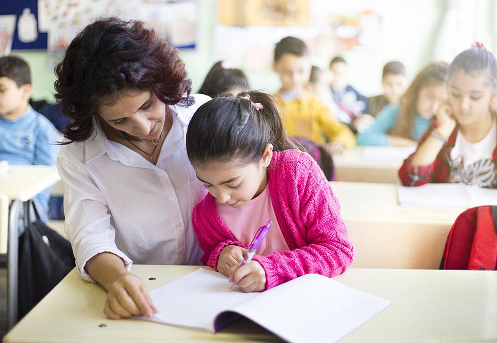 Teacher teaches her student to write at a preschool & childcare center Serving Erie, CO & Kansas City, KS