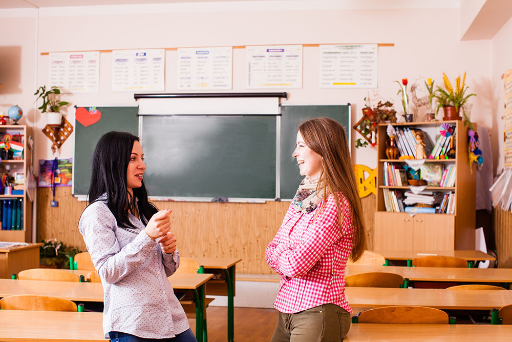 Two smiling young women teacher standing at a preschool & childcare center Serving Erie, CO & Kansas City, KS