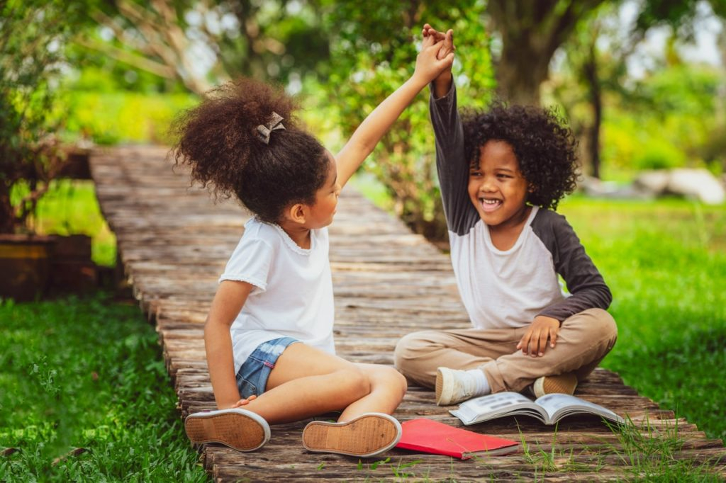 Two happy kids reading outside at a preschool & childcare center Serving Erie, CO & Kansas City, KS