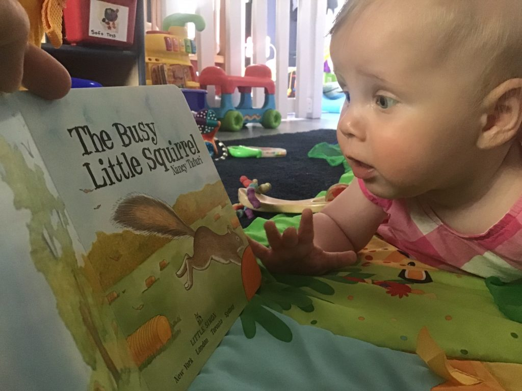 Happy toddler reading the book at a preschool & childcare center Serving Erie, CO & Kansas City, KS