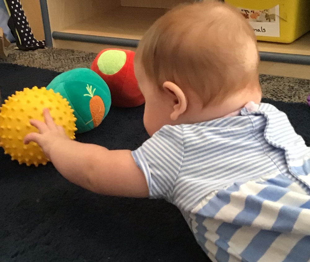 Cute toddler playing balls at a preschool & childcare center Serving Erie, CO & Kansas City, KS
