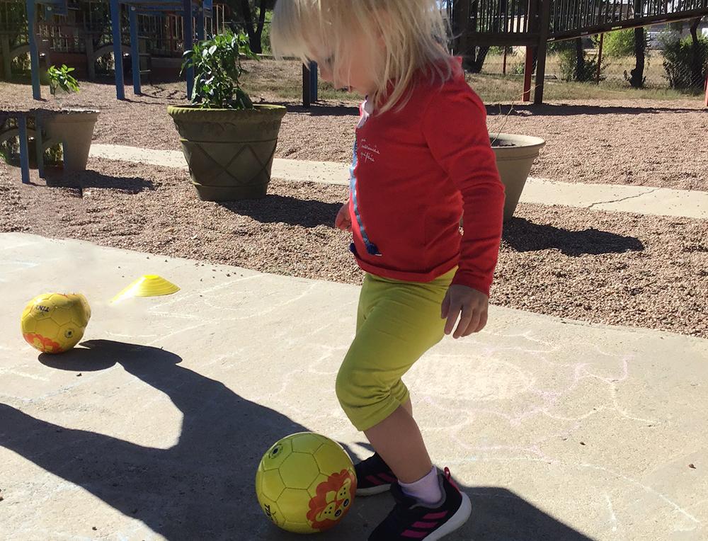 Cute little girl playing ball outside at a preschool & childcare center Serving Erie, CO & Kansas City, KS