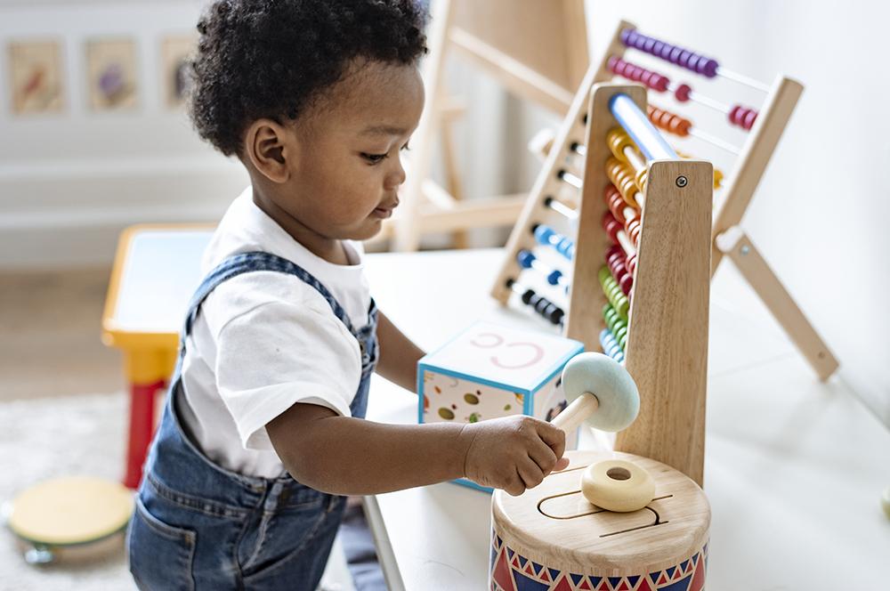 Cute little boy toddler playing at a preschool & childcare center Serving Erie, CO & Kansas City, KS