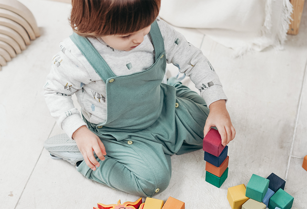 Cute little toddler playing colorful blocks at a preschool & childcare center Serving Erie, CO & Kansas City, KS