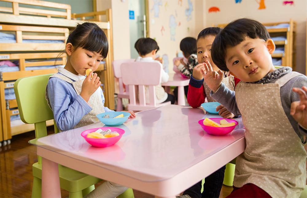 Happy kids eating at a preschool & childcare center Serving Erie, CO & Kansas City, KS