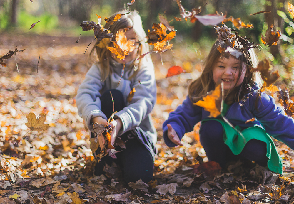 Two girls playing leaves at a preschool & childcare center Serving Erie, CO & Kansas City, KS