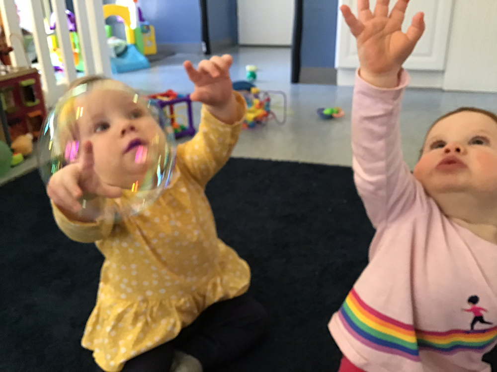 Two little cute toddlers playing bubbles at a preschool & childcare center Serving Erie, CO & Kansas City, KS
