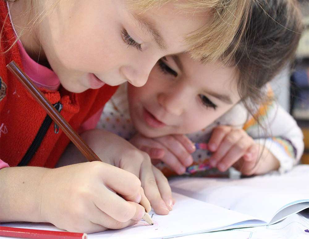 Two kids learning to write at a preschool & childcare center Serving Erie, CO & Kansas City, KS
