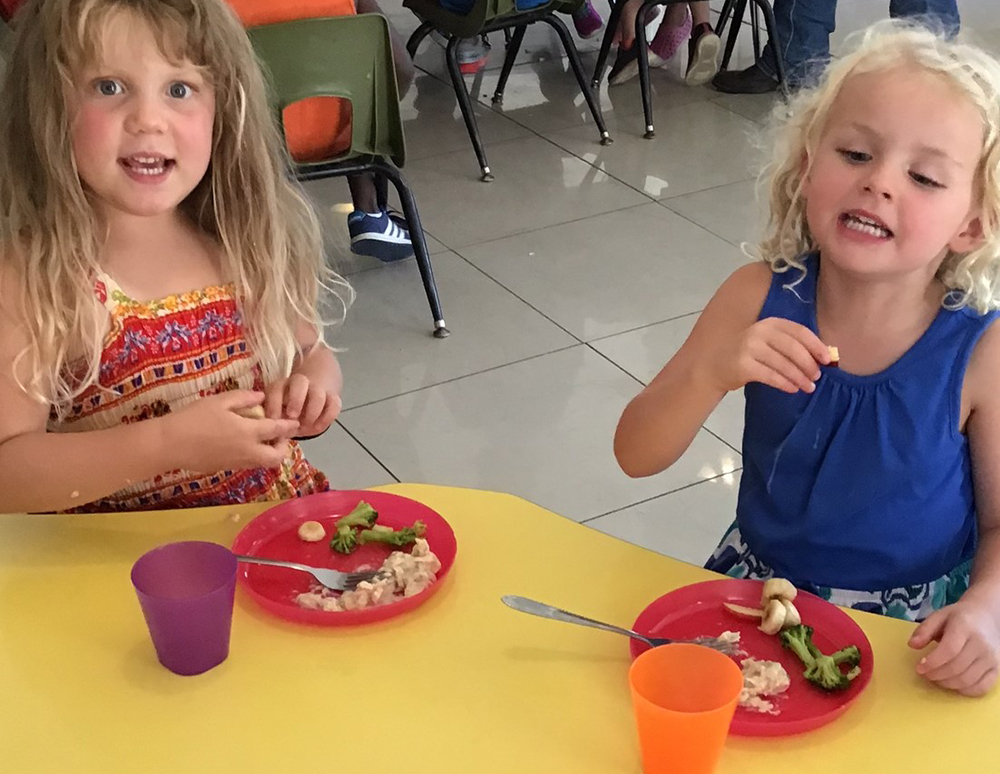 Two cute little toddlers eating on yellow table at a preschool & childcare center Serving Erie, CO & Kansas City, KS
