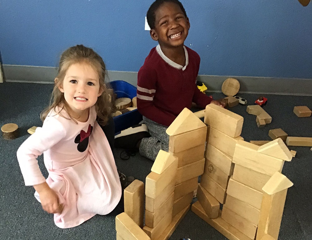 Two toddlers playing wood blocks at a preschool & childcare center Serving Erie, CO & Kansas City, KS