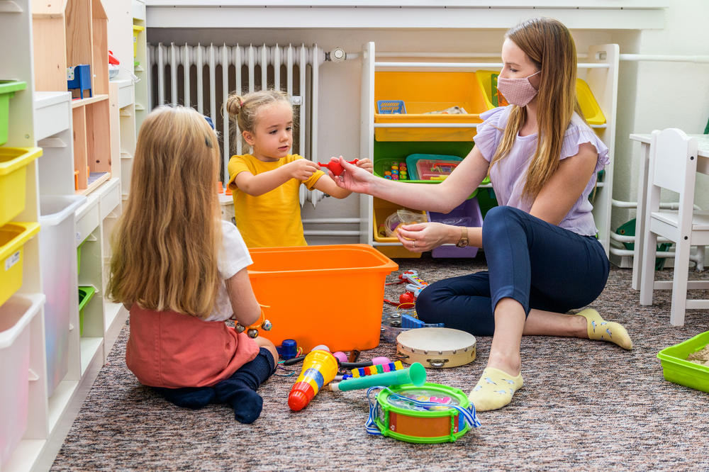 Teacher and two toddler girls playing and learning at a preschool & childcare center Serving Erie, CO & Kansas City, KS