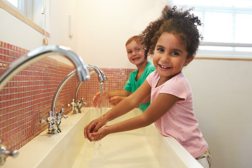 Happy kids washing hands at a preschool & childcare center Serving Erie, CO & Kansas City, KS