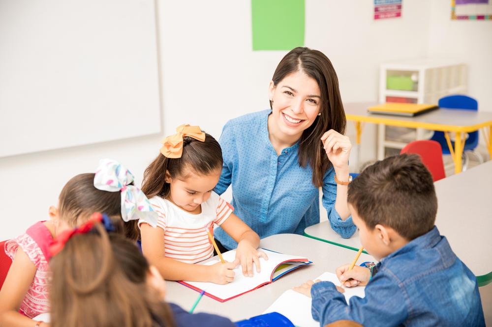Teacher teaching her students writing at a preschool & childcare center Serving Erie, CO & Kansas City, KS