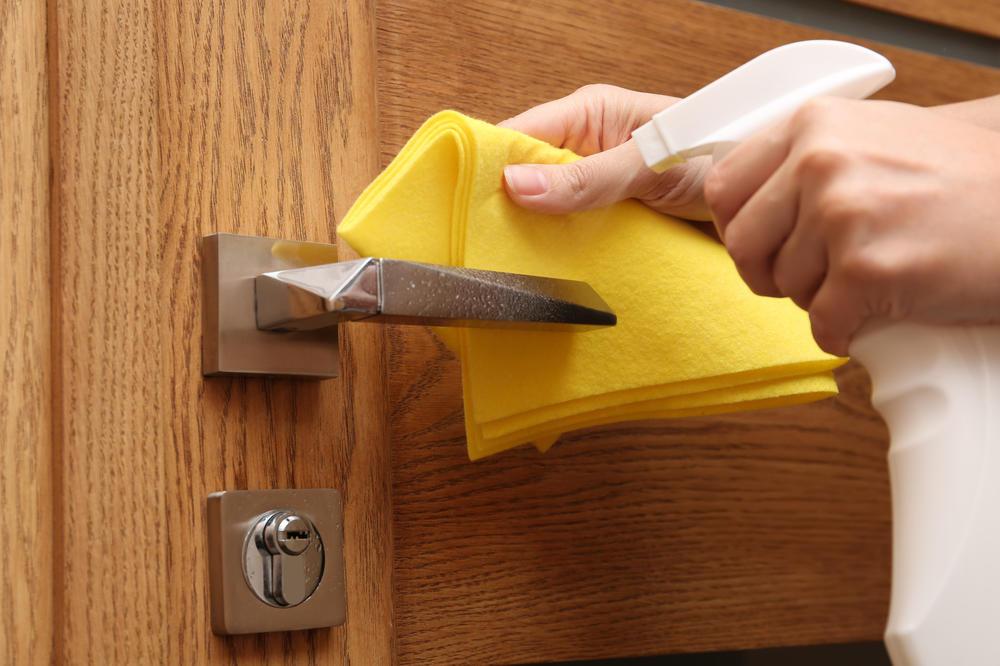 Sanitizing door knob at preschool & childcare center Serving Erie, CO & Kansas City, KS