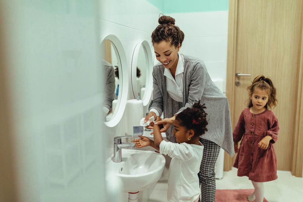 Teacher and little girls washing hands at preschool & childcare center Serving Erie, CO & Kansas City, KS