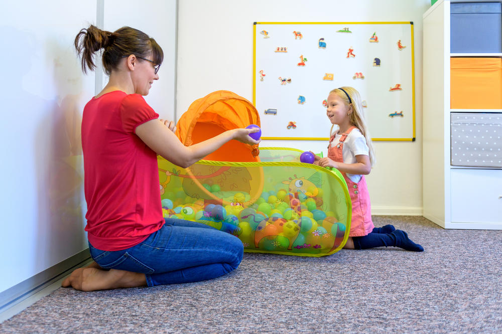 Teacher and cute toddler plays and learning at preschool & childcare center Serving Erie, CO & Kansas City, KS