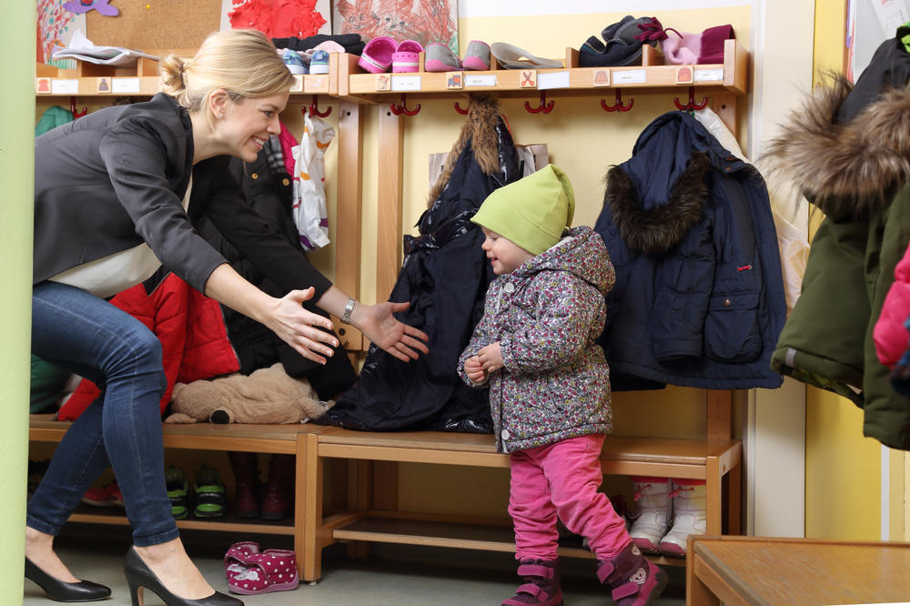Mother and happy little child wearing jacket at preschool & childcare center Serving Erie, CO & Kansas City, KS