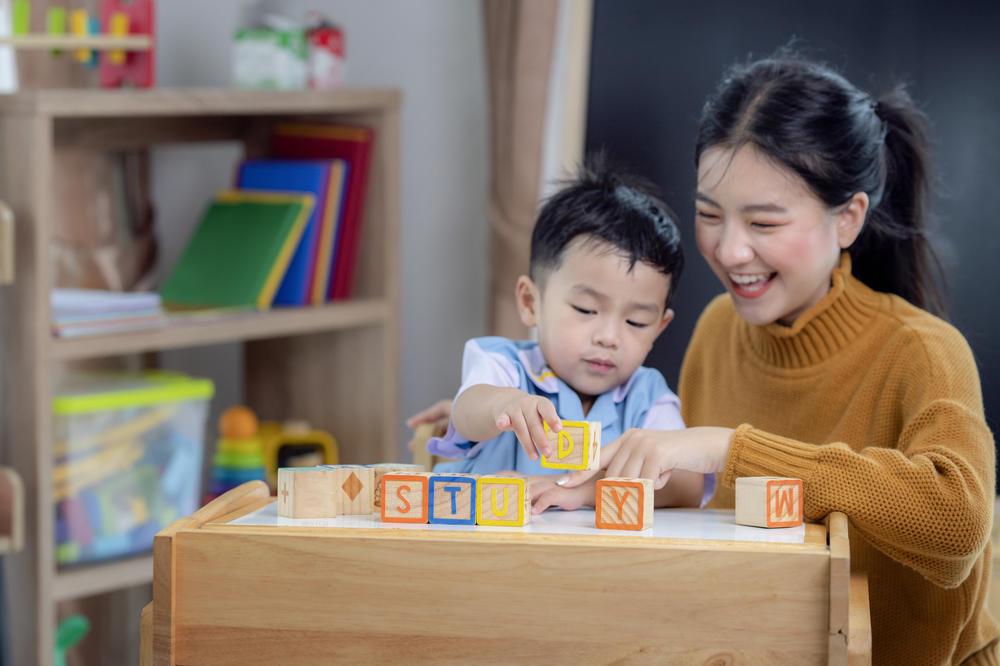 Cute little boy and teacher learning alphabets at preschool & childcare center Serving Erie, CO & Kansas City, KS