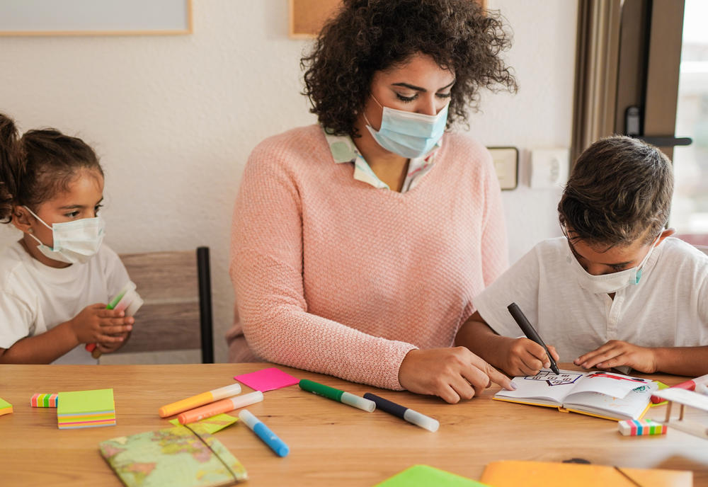 Kids and the teacher doing coloring activity at preschool & childcare center Serving Erie, CO & Kansas City, KS
