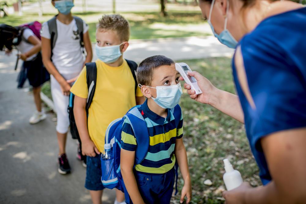 Teacher and Kids checking temperature at preschool & childcare center Serving Erie, CO & Kansas City, KS