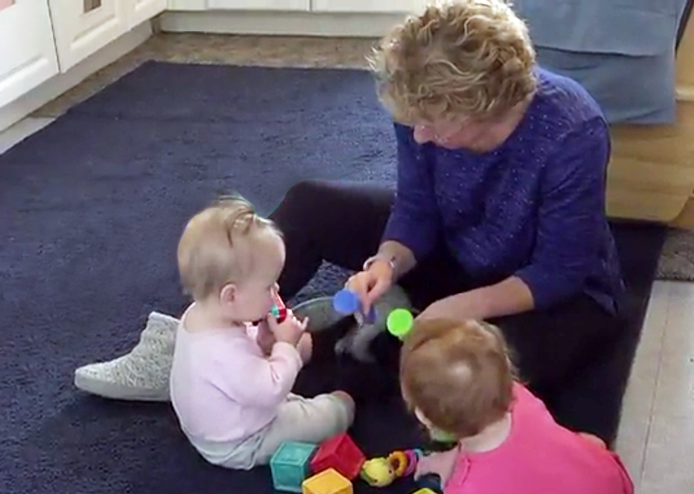 Teacher and toddlers playing a colorful toys in preschool & childcare center Serving Erie, CO & Kansas City, KS