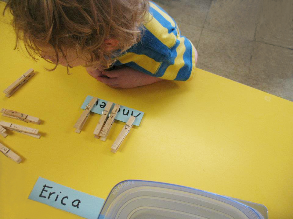 Toddler leaning on a yellow table learning at a preschool & childcare center Serving Erie, CO & Kansas City, KS