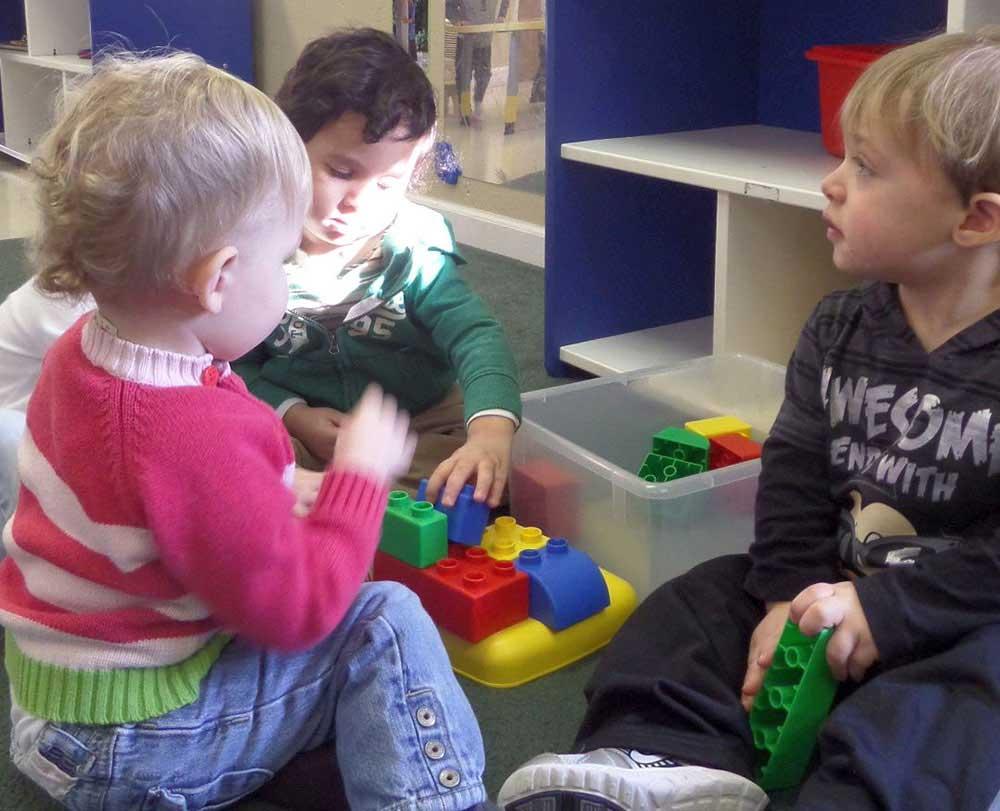 Children playing colorful toys in preschool & childcare center Serving Erie, CO & Kansas City, KS