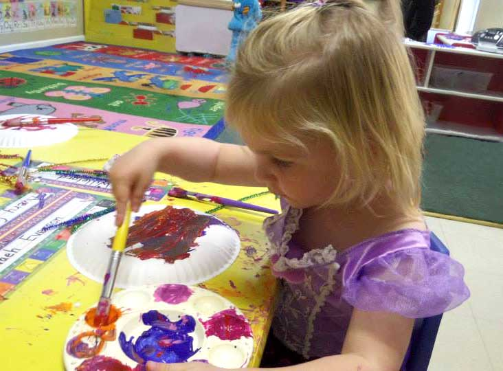 Child playing paints in preschool & childcare center Serving Erie, CO & Kansas City, KS